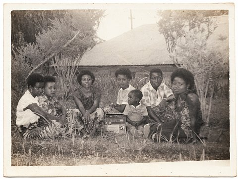 Teachers listen to the radio in the school garden. From a Katembera family photo album. Photographer unknown. Bukavu, D.R.C., 1982.