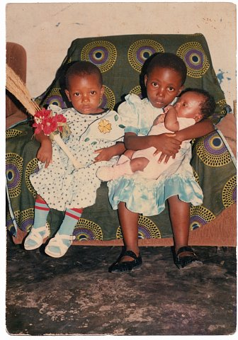 Faradja, Rebecca and Daniel Katembera. From a Katembera family photo album. Photographer unknown. Kinshasa, D.R.C., 1990.