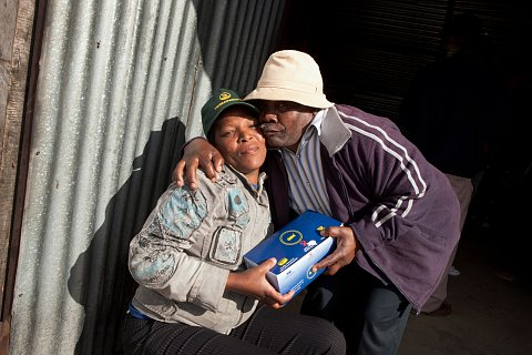 "A couple in Cape Town, South Africa embrace after receiving a package of free condoms distributed by the SONKE Gender Justice Network on July 26, 2012. <br>  <a href=""http://sarahstacke.photoshelter.com/gallery/SONKE/G00007TeU5ghJzxk"">View Archive</a>"