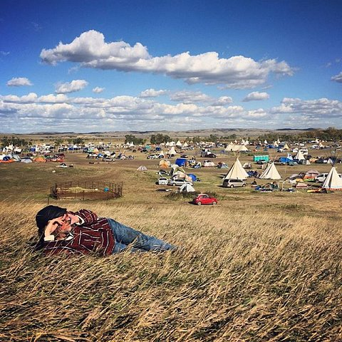 "A man talks on the phone on ""Facebook hill"", which overlooks the Sacred Stone camp near Cannon Ball, ND. ""Facebook hill"" is one of the few spots in the camp where the thousands who have gathered to protest the Dakota Access Pipeline can get a cell signal. #northdakota #NoDAPL #standingrocksioux"