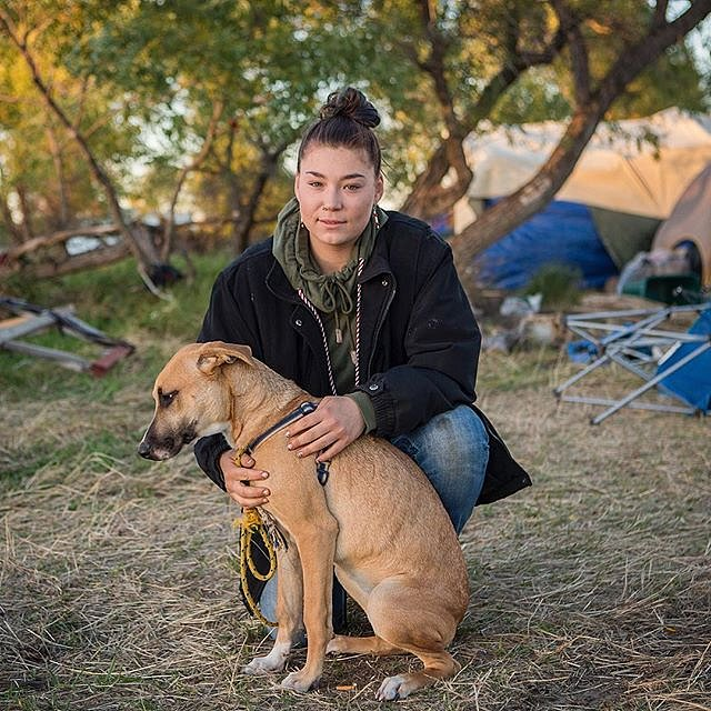 """Adriana Furlong 21, is a member of the Alaskan Aleut Tribe. She lives in Seattle, Wash. and traveled to the Oceti Sakowin camp near Cannon Ball, N.D. to join the #NoDAPLE protests. Here, Furlong sits with a dog she calls """"Mama"""" or """"MaeMae,"""" who she found"""