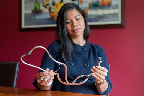 Dr. Maryam Shapland, a fourth generation physician, holds her grandfather's stethoscope while sitting at her kitchen table in Saint Paul, Minn. Shapland began working at a life insurance company after the long hours and stress of her job as an emergency physician began taking a toll. May 18, 2017.