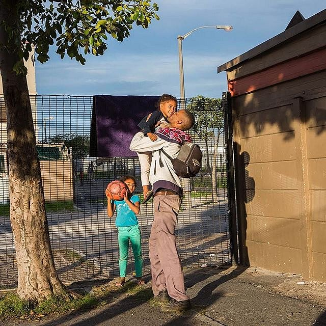 Siraaj Abrams lifts his daughter, Ronel Pietersen, into the air after getting home from work. His daughter Chelsea stands nearby. Manenberg, South Africa. June 2018. #forcedgeographies #personalproject #southafrica #capetown #africa #lovefrommanenberg #ri