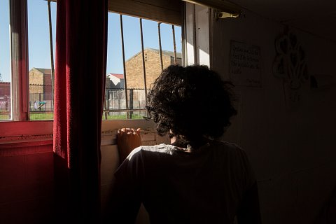 Tosha Adams, 17, looks out the window of her bedroom. <br>Manenberg, June 2018.