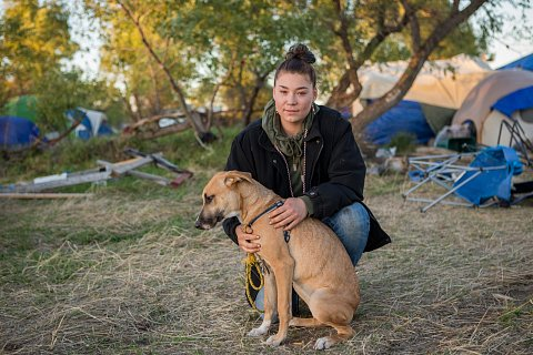"Adriana Furlong, 21, is a member of the Alaskan Aleut Tribe. She lives in Seattle, Wash. and traveled to the Oceti Sakowin camp near Cannon Ball, N.D. to join the #NoDAPL protests. Here, Furlong sits with a dog she calls ""Mama"" or ""MaeMae,"" who she found in the camp. She's searching for the dog's owners. September 25, 2016."